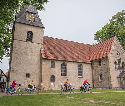 Radfahrer vor der Kirche in Bockhorst