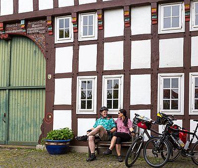 Radfahrer machen an einem Fachwerkhaus Pause